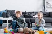 rozkošný šťastné děti sedí na podlaze a hraní s hračkami doma