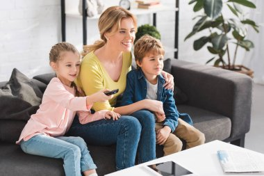 happy mother and cute smiling kids using remote controller and watching tv together