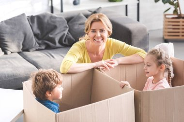 happy mother smiling at camera while kids playing in cardboard boxes