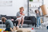 Erschöpfte Mutter mit Kleinkind auf Couch sitzend und in die Kamera blickend, während freche Geschwister zu Hause spielen