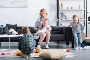 tired mother with infant child sitting on couch and looking at naughty siblings playing at home