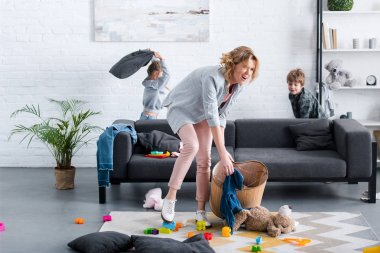 emotional tired mother putting toys in basket while naughty kids playing behind