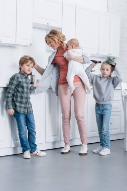 exhausted mother with infant kid cooking while naughty children playing in kitchen