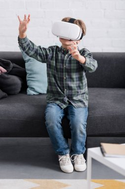 Child sitting on couch and using virtual reality headset at home stock vector
