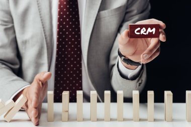 partial view of businessman holding brick with 'crm' word and preventing wooden blocks from falling