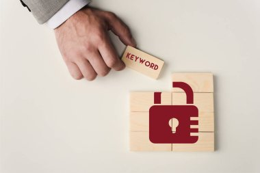Partial view of man holding brick with 'keyword' lettering over wooden blocks with lock icon isolated on white stock vector