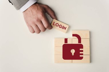 Partial view of man holding brick with 'login' lettering over wooden blocks with lock icon isolated on white stock vector