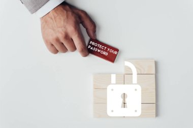 partial view of man holding brick with 'protect your password' lettering over wooden blocks with lock icon isolated on white