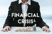 Fényképek levágott kilátás üzletasszony fa tömb és a pénz roll asztalra, és a pénzügyi válság felirat-ra előtér