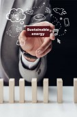 Photo partial view of man holding red brick with words sustainable energy isolated on black, icons on foreground