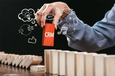 cropped view of woman picking red block with word 'crm' out of wooden bricks, icons on foreground