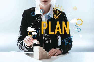 Cropped view of woman building career ladder with wooden blocks, icons and 'plan' lettering on foreground stock vector