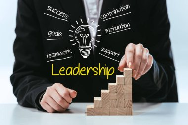 cropped view of woman with wooden career ladder, components of leadership on foreground