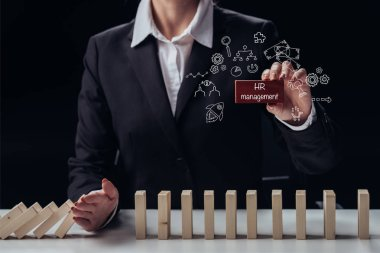 cropped view of businesswoman holding red brick with words 'HR management' while preventing wooden blocks from falling, icons on foreground