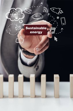 partial view of man holding red brick with words 'sustainable energy' isolated on black, icons on foreground