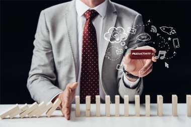 cropped view of businessman preventing wooden blocks from falling while holding brick with word 'productivity', icons on foreground