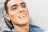 close up of smiling african american man in dental clinic