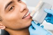 zblízka veselá afroamerické muže s úsměvem poblíž zuby barevnou paletu