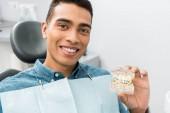 schöner afrikanisch-amerikanischer Mann mit Zahnkiefer-Modell mit Zahnspange