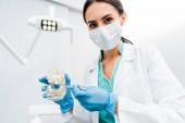 weibliche Zahnarzt zeigen dental Kiefer Modell mit Klammern