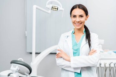 beautiful dentist standing with crossed arms in dental clinic