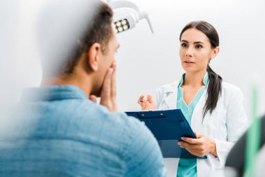 selective focus of female dentist standing with clipboard and talking with african american patient having toothache