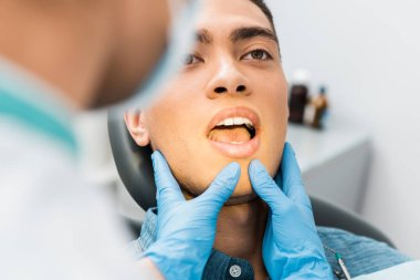 selective focus of female dentist hands in latex gloves touching face of handsome african american man with open mouth