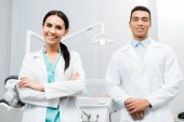 Fotografie cheerful  female doctor standing near african american coworker in white coat with crossed arms