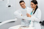 Fotografie cheerful multicultural doctors looking at digital tablet