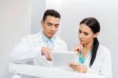 Fotografie serious multiethnic doctors looking at digital tablet