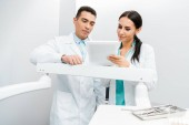 Fotografie multicultural doctors standing in white coats and looking at digital tablet