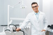schöner afrikanisch-amerikanischer Zahnarzt lächelnd und mit der Hand in der Tasche stehend