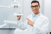Fotografie handsome african american doctor in glasses pointing at toothpaste in dental clinic