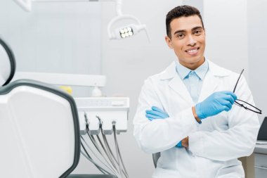 handsome african american stomatologist holding glasses and standing with crossed arms