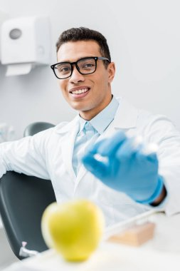 selective focus of male african american dentist wearing latex glove near sweet apple