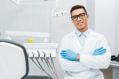 handsome african american dentist in glasses standing with crossed arms