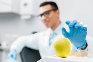 selective focus of hand of male african american dentist wearing latex glove near sweet apple