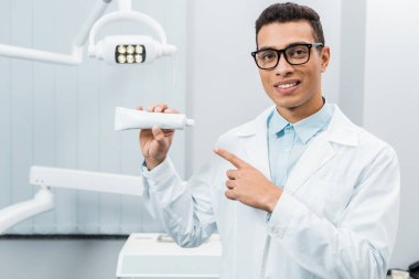 Handsome african american doctor in glasses pointing at toothpaste in dental clinic stock vector