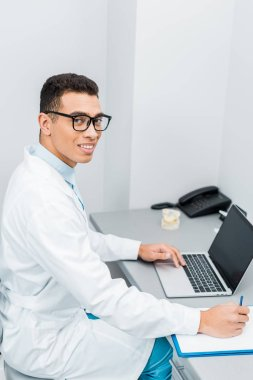 cheerful african american doctor making notes and using laptop