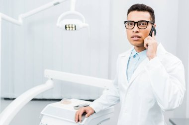 serious african american dentist in glasses talking on smartphone