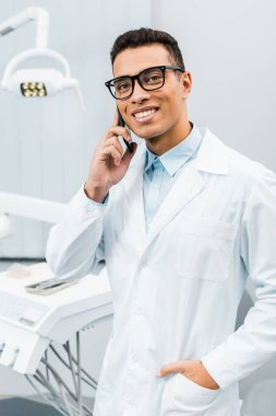 handsome african american doctor in glasses talking on smartphone with hand in pocket