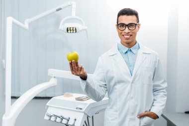 smiling african american dentist with hand in pocket holding apple