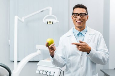 handsome african american doctor in glasses pointing at apple
