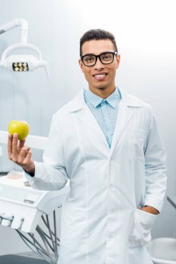 handsome african american dentist with hand in pocket holding apple