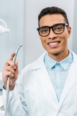 smiling african american dentist in glasses and white coat holding drill