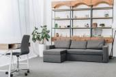 modernes Wohnzimmer mit Sofa, Ablagen und Arbeitsbereich