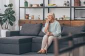 zasněný starší žena sedí na pohovce s chůzi hůl v obývacím pokoji