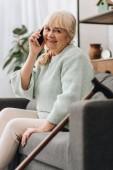 senior donna allegra che comunica su smartphone, stando seduti sul divano