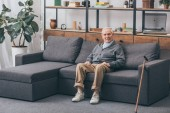 starší muž s šedými vlasy sedí na pohovce v obývacím pokoji