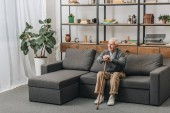 Fotografie happy senior man smiling and holding walking cane while sitting on sofa